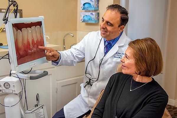 Dentist showing patient gum recession